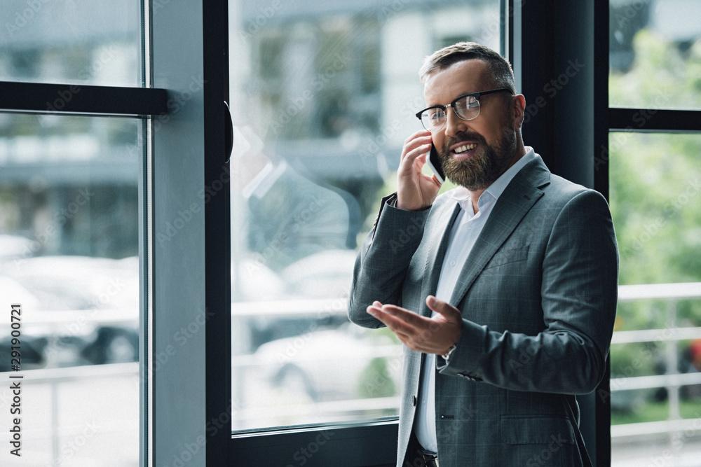 Fototapeta handsome businessman in formal wear and glasses talking on smartphone