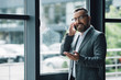 handsome businessman in formal wear and glasses talking on smartphone