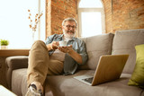 Senior man working with laptop at home - concept of home studying. Caucasian male model sitting on sofa and having coffee break while serfing in internet, watching cinema or webinar, online lessons.