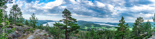 Very wide panorama over wild Scandinavian mountains with pine tree forest, the village and two sea bays, summer day with heavy dramatic clouds, North Sweden