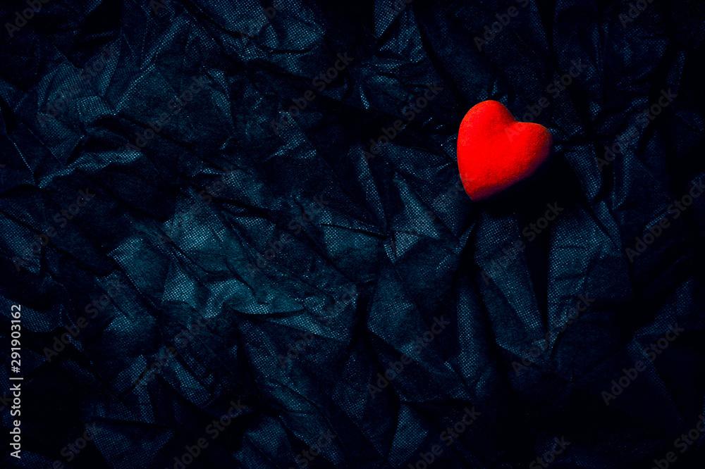 Fototapeta Red Heart on Wrinkled Dark Blue Background. Happy Valentine's Day, Love. Moody Romantic Halloween Concept.