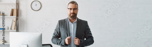 panoramic shot of handsome businessman in formal wear looking at camera Canvas Print