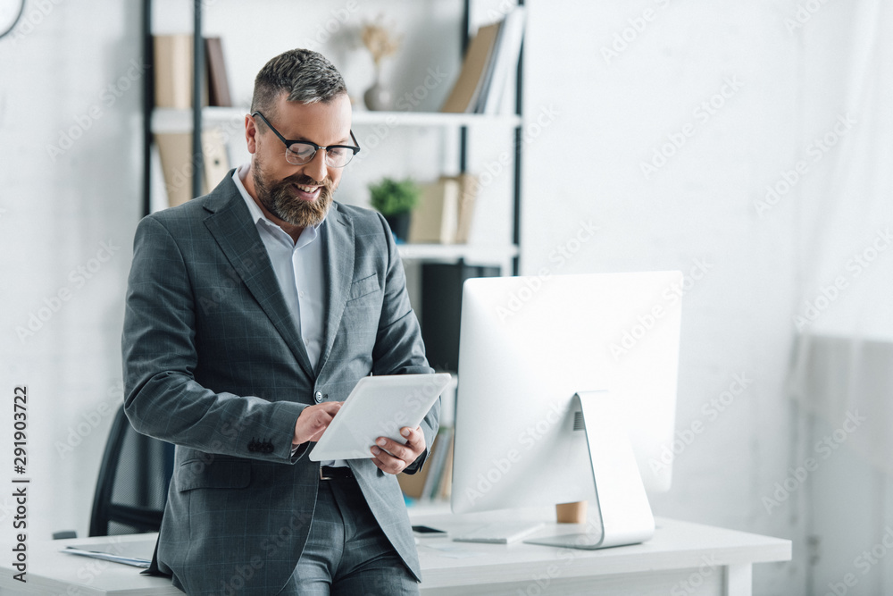Fototapeta handsome businessman in formal wear using digital tablet in office