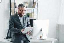 Handsome Businessman In Formal Wear Using Digital Tablet In Office