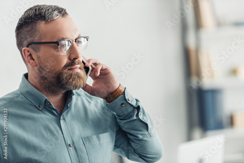 Fotografía  handsome businessman in shirt and glasses talking on smartphone in office