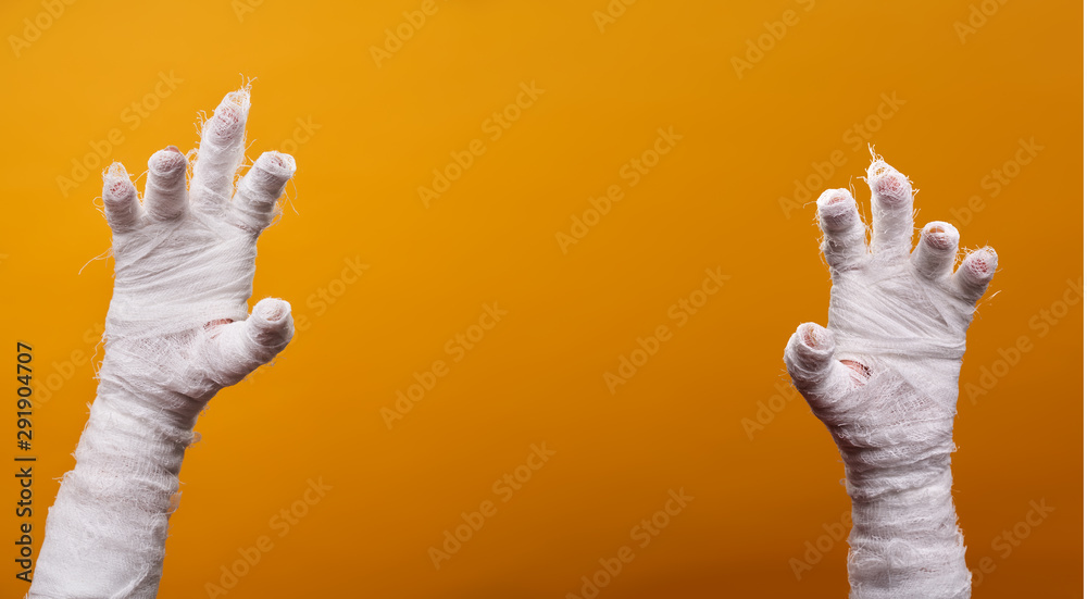 Fototapeta Photo of two mummy hands on empty orange background .