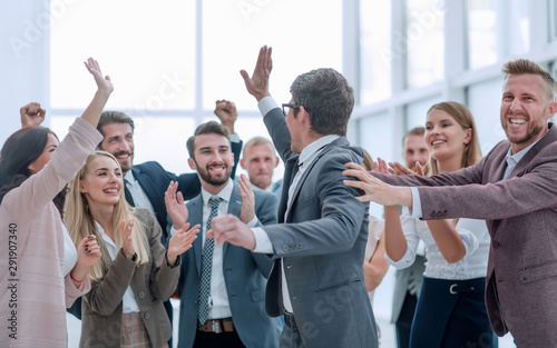Photo group of cheerful company employees congratulating their colleague
