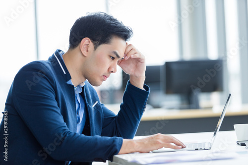 Fototapety, obrazy: Stressed businessman worked with laptop computer and having a headache after business losses In the office room background.