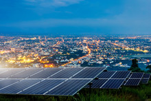 Solar Panel With City Night Architecture Electric Energy Light Background,clean Alternative Power Energy Concept.