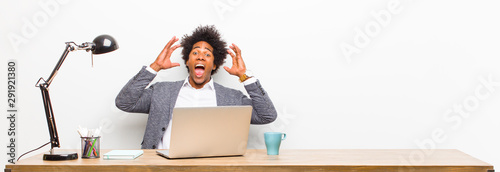 Fotografie, Obraz  young black businessman screaming with hands up in the air, feeling furious, fru