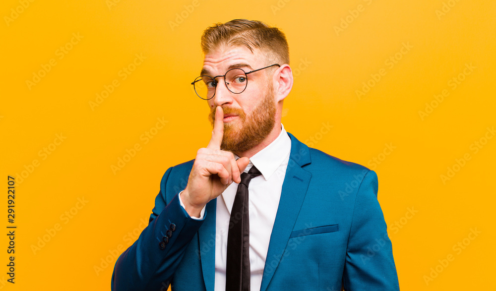 Fototapeta young red head businessman asking for silence and quiet, gesturing with finger in front of mouth, saying shh or keeping a secret against orange background