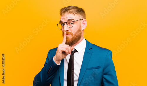 Fototapeta  young red head businessman asking for silence and quiet, gesturing with finger i