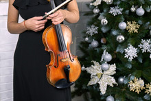 Female Musician Violinist With Her Violin On The Christmas Tree Background