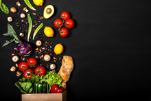 Shopping Paper Bag Full Of Different Fresh Vegetables And Bread On A Black Background. Purchases Concept. Healthy Food Organic Selection. Top View, Copy Space.