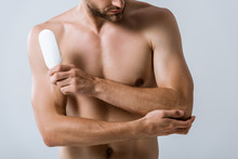 Cropped View Of Shirtless Man Holding Bottle Of Ointment And Touching Elbow Isolated On Grey