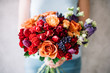 Very nice young woman holding a beautiful blossoming flower bouquet of fresh roses, peony, carnations, eustoma in vivid orange and red colours on the grey wall background