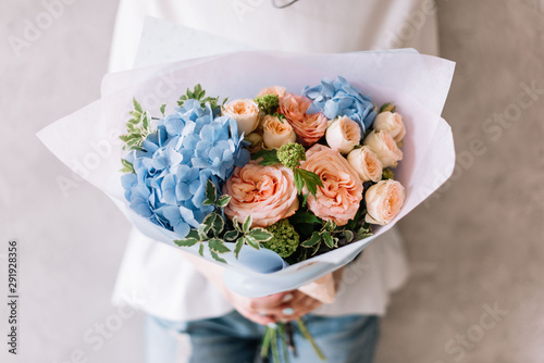 Very nice young woman holding a beautiful blossoming flower bouquet of fresh hydrangea, roses, carnations in pink and light blue colours on the grey wall background  © anastasianess