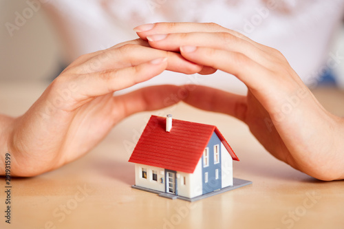 Hands protect house as insurance concept Fototapete