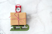 Christmas Gift Wrapped In Brown Craft Paper And Clock On Wooden Sleigh Christmas Toys On Gray Marble Background. New Year, Christmas And Winter Concept. Flat Lay, Top View.