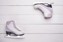 Close-up Photo Of Professional Ice Skates Lying On A White Wooden Background.