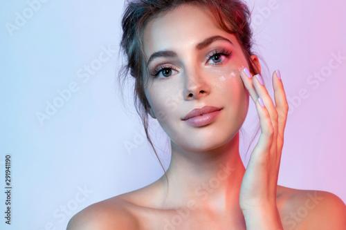 Cuadros en Lienzo Cute woman with natural make-up applying moisturizing facial cream