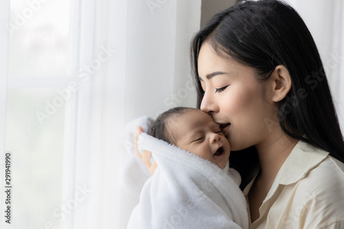 Portrait of asian young mother kissing her cute newborn baby in white bed room Fototapete
