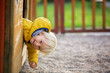 canvas print picture - Blonde little toddler child in yellow jacket, playing on the playground