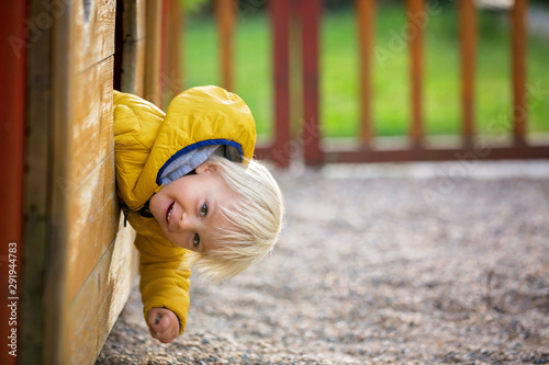 Obraz Blonde little toddler child in yellow jacket, playing on the playground - fototapety do salonu