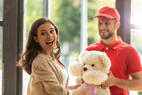 selective focus of positive girl receiving teddy bear from bearded man in cap