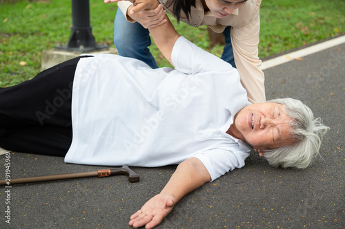 Photo Asian elderly woman with walk stick on floor after falling down,young assistant