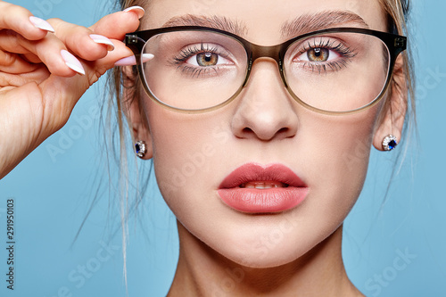 Portrait of attractive young woman in glasses on blue background Wallpaper Mural