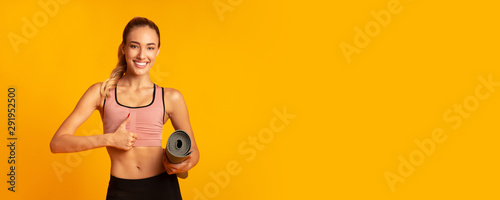 Girl Holding Rolling Mat Gesturing Thumbs-Up On Yellow Background, Panorama Obraz na płótnie