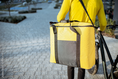 Pays d Asie Courier delivering food in a yellow thermo bag with a bicycle in the city, close-up focused on the bag with copy space