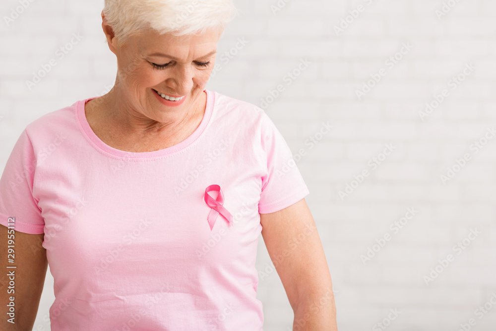 Fototapeta Elderly Woman Looking At Pink Cancer Ribbon On T-Shirt, Indoor