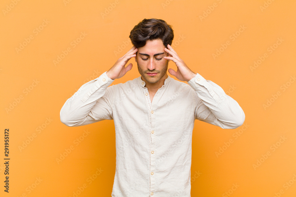 Fototapeta young handsome man looking concentrated, thoughtful and inspired, brainstorming and imagining with hands on forehead against orange background