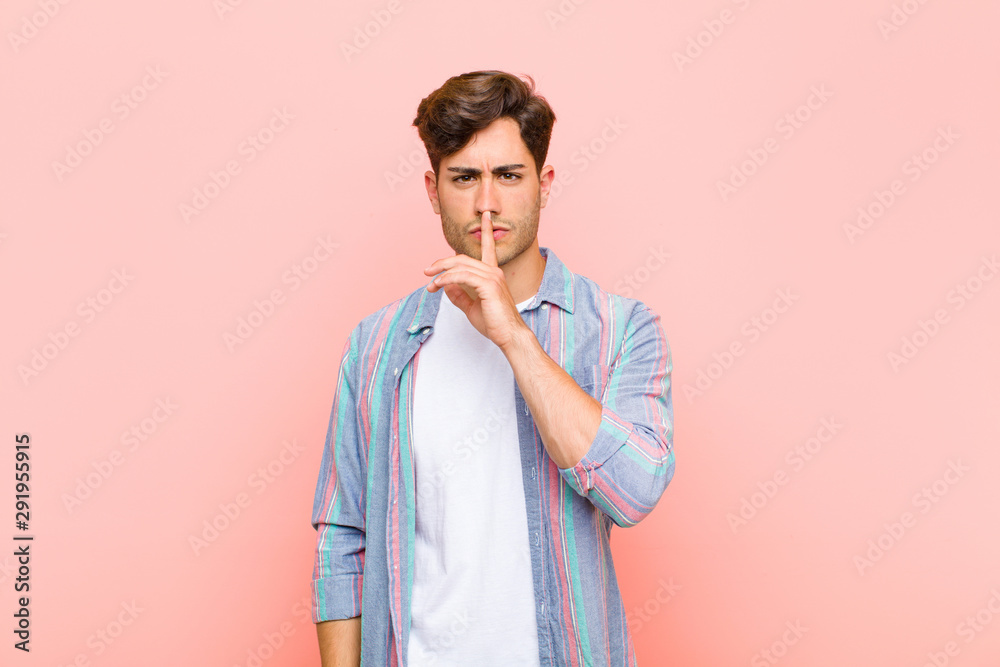 Fototapeta young handsome man looking serious and cross with finger pressed to lips demanding silence or quiet, keeping a secret against pink background