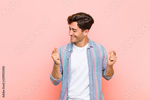 young handsome man smiling, feeling carefree, relaxed and happy, dancing and listening to music, having fun at a party against pink background - 291955900