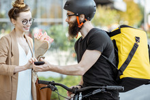 Courier Delivering Fresh Flowers To A Young Business Woman On A Bicycle Wearing Delivery Backpack. Fresh Floral Delivery Concept