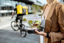 Businesswoman Holding Lunchboxes With Fresh Takaway Food Outdoors. Male Courier On A Bicycle On The Background. Takeaway Restaurant Food Delivery Concept