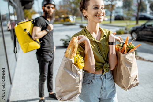 Young and happy woman carrying bags full of fresh food received from a delivery man. Courier standing with delivery bag on the background - 291960563