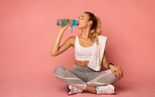 Fitness Woman Drinking Water Sitting On Floor In Studio