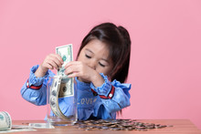 The Little Girl Is Putting The Banknote In A Clear Glass Jar, Money Saving Concept.