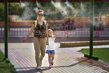 Young Mother With Her Daughter In Hot Weather, Cool Off At The Gates Of Climate Control In The Water Park. Aerosol Spraying Of Water Jets, Spraying Of Cooling Water. Air Conditioning Nozzle
