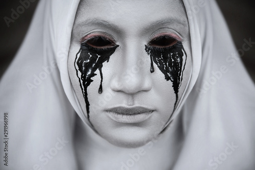Fotografía A gloomy portrait of a ghostly pale nun in white robes with black eye sockets and black smudges under them