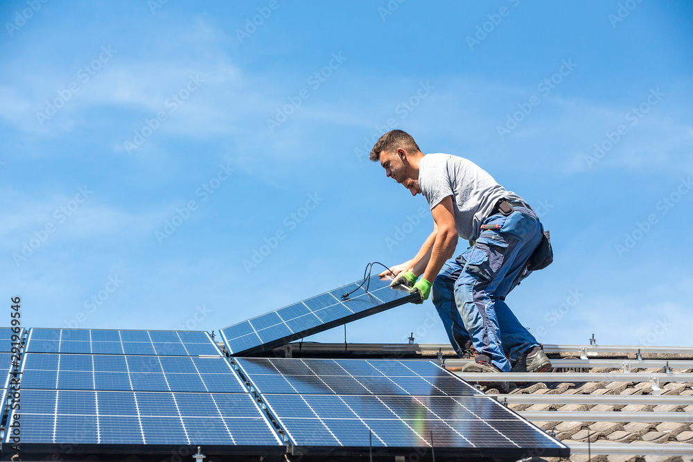 Fototapety, obrazy: Installing solar photovoltaic panel system. Solar panel technician installing solar panels on roof. Alternative energy ecological concept.