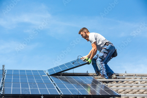 Obraz Installing solar photovoltaic panel system. Solar panel technician installing solar panels on roof. Alternative energy ecological concept. - fototapety do salonu
