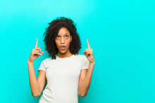 Young Black Woman Looking Shocked, Amazed And Open Mouthed, Pointing Upwards With Both Hands To Copy Space Against Blue Wall
