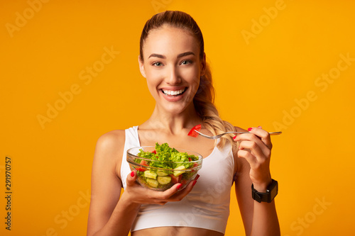 Pinturas sobre lienzo  Fitness Girl Eating Vegetable Salad Standing Over Yellow Background