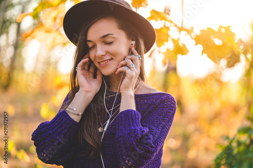 Happy attractive autumn brunette woman in a brown hat and in a knitted sweater wearing silver rings with turquoise stone enjoys listening to autumn music on headphones outdoors in fall - 291972957