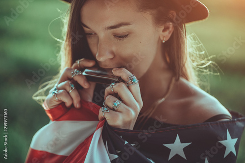 Portrait of boho chic woman in hat with american flag wearing silver rings with turquoise stone playes on harmonica outdoors. Jewelry indie girl with hippie style and boho fashion. Travel to america - 291973160